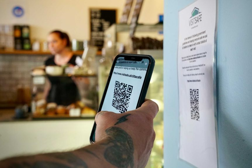 Tattooed hand holding phone with QR code in a cafe