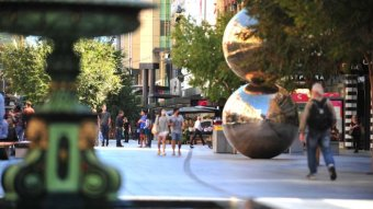 A pedestrian mall with a fountain and a sculpture of two silver balls