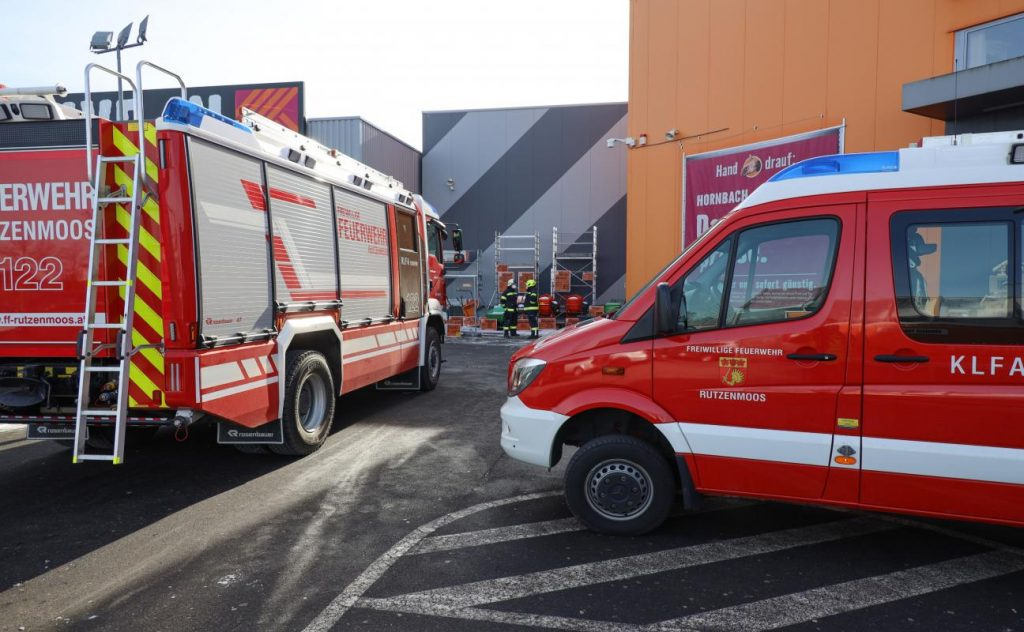 Crowding under a snack vending machine: Firefighters on duty to rescue people at a hardware store in Rega