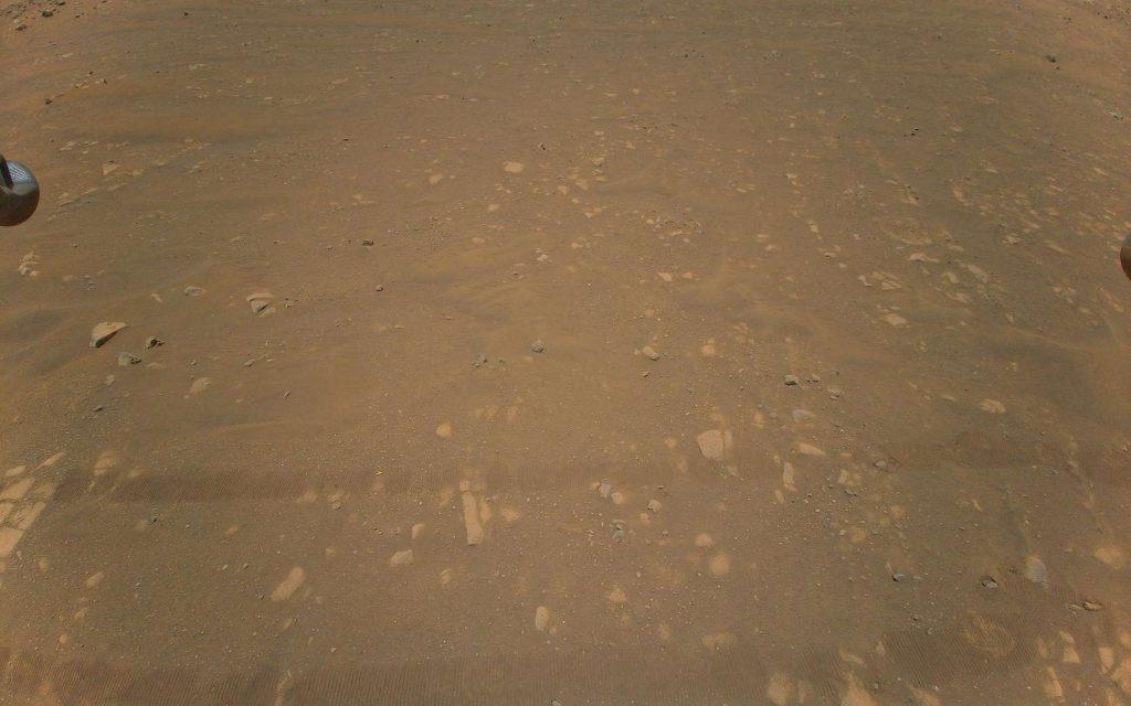 Sur cette troisième image couleur renvoyée par Ingenuity aux ingénieurs de la Nasa, on devine encore les traces laissées par le rover Perseverance au sol. Mais d'autres images le montrent bien plus clairement. © Nasa, JPL-Caltech
