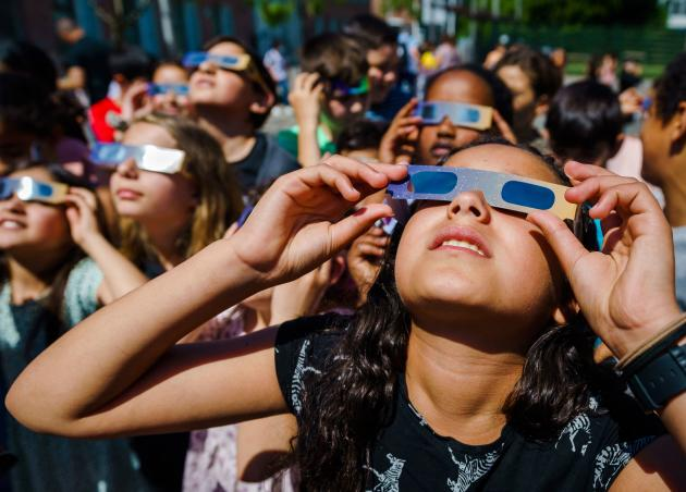 Children observe a partial eclipse on June 10, 2021 in Sheidam, the Netherlands.