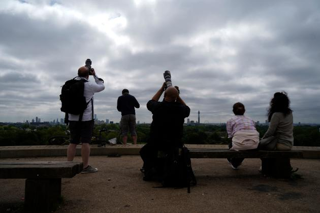 People attempt to photograph a partial solar eclipse on June 10, 2021 at Primrose Hill Park in London.